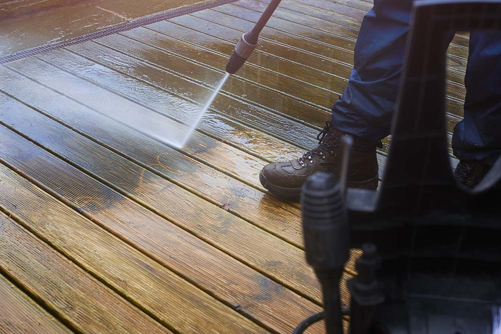 Man in boots power washing a deck