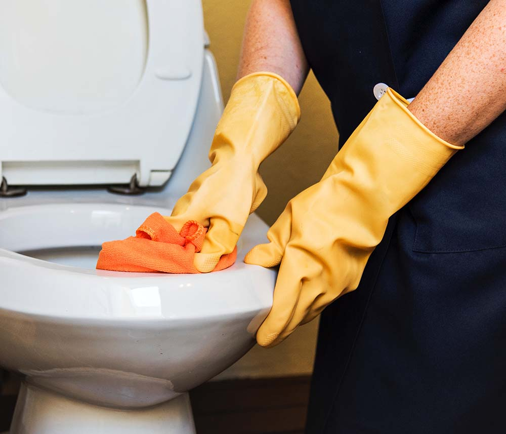 Gloved worker cleaning toilet
