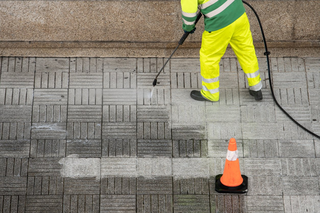 Worker cleaning the street sidewalk with high pressure water jet
